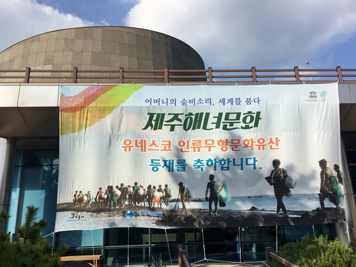 A banner outside the front of the Haenyeo Museum congratulating the UNESCO World Intangible Cultural Heritage status